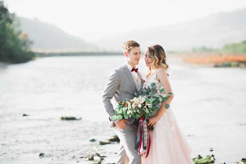 Novia rubia feliz elegante elegante y novio magnífico en el fondo de un río hermoso en las montañas foto de archivo libre de regalías
