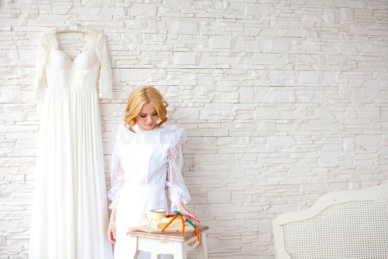 Novia rubia hermosa cerca de la pared de ladrillo blanca fotografía de archivo libre de regalías