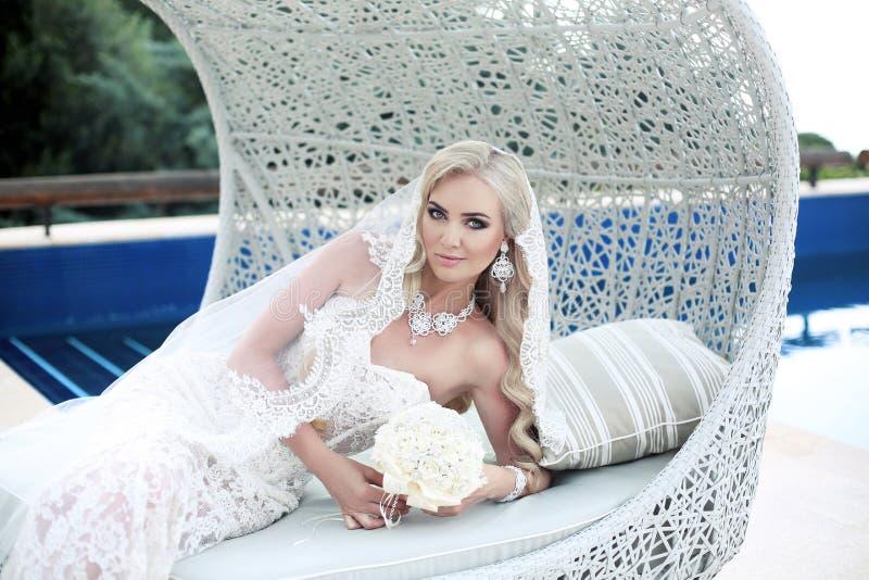 Novia rubia hermosa del retrato de boda que miente en el sofá de la playa en f imagen de archivo