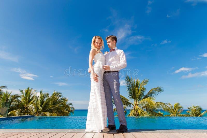 Novia rubia hermosa en el vestido de boda blanco y el danc del novio imagen de archivo