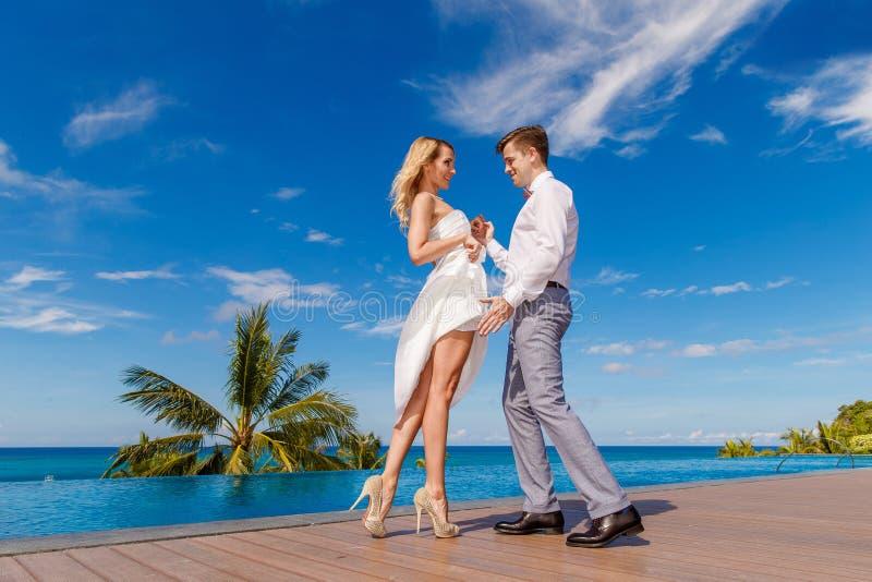 Novia rubia hermosa en el vestido de boda blanco y el danc del novio imagenes de archivo