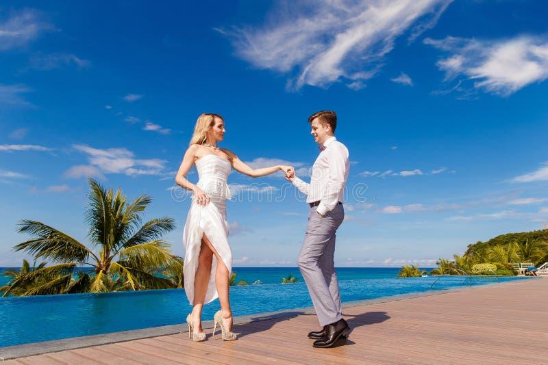 Novia rubia hermosa en el vestido de boda blanco y el danc del novio imagen de archivo libre de regalías