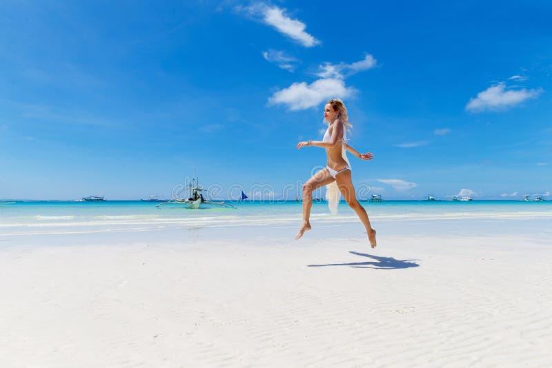 Novia rubia hermosa en un bikini blanco y un velo que se divierten o fotografía de archivo