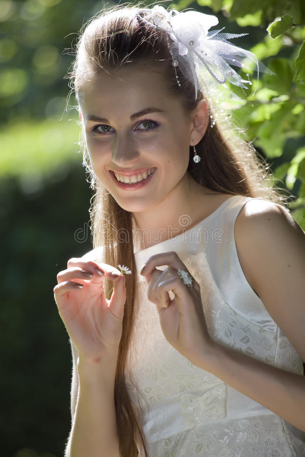 Novia sonriente con la planta de la margarita fotografía de archivo libre de regalías