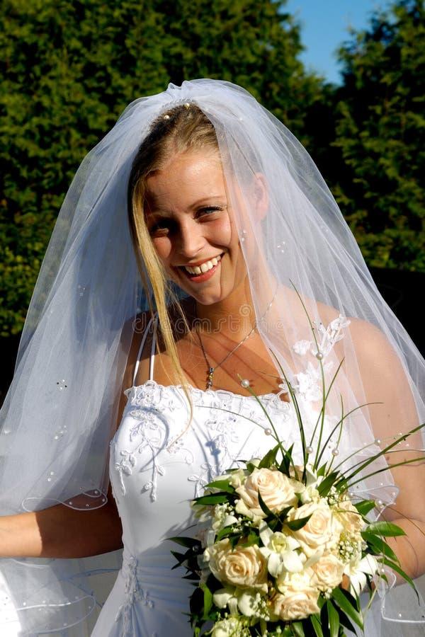 Novia sonriente feliz de la boda con el ramo. foto de archivo