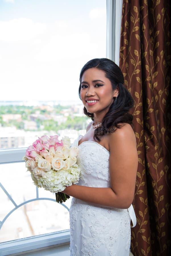 Novia sonriente hermosa en la ventana con el ramo imagen de archivo libre de regalías
