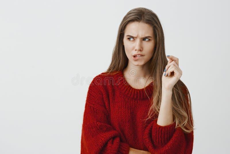 Novia sospechosa que intenta pensar encima de manera de escoger la contraseña del smartphone Retrato de apuesto ansioso enfocada fotos de archivo