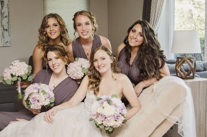 Novia y damas de honor hermosas en el sofá foto de archivo libre de regalías