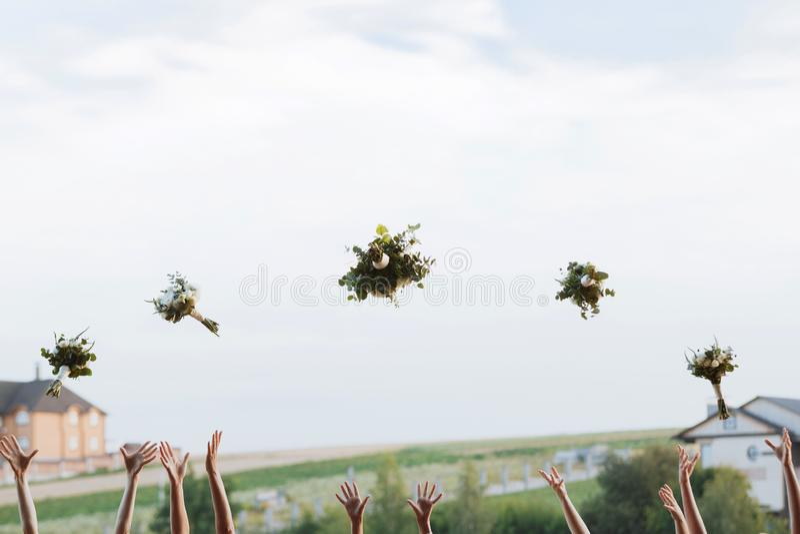 Novia y damas de honor que lanzan para arriba ramos en el cielo, espacio para el texto Momento alegre Mañana de la boda fotografía de archivo