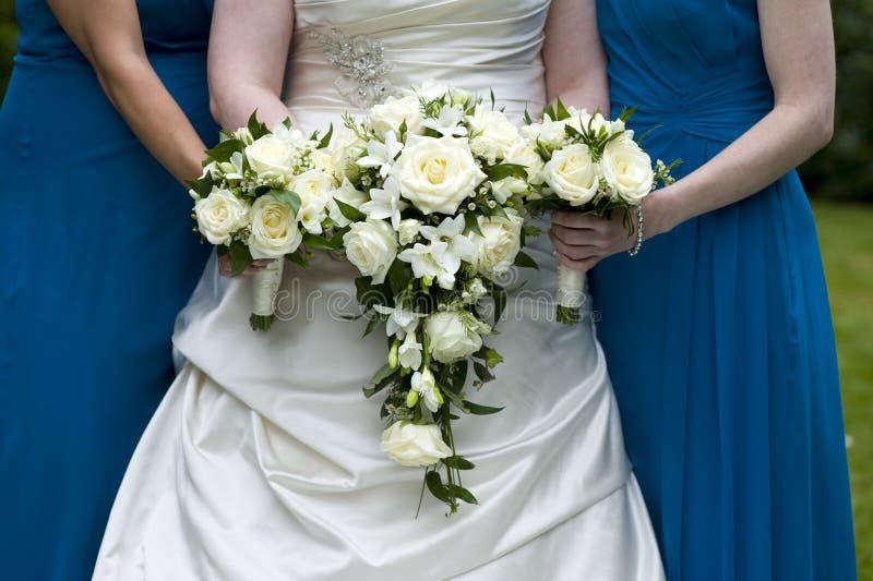 Novia y damas de honor que sostienen ramos de la boda imagen de archivo