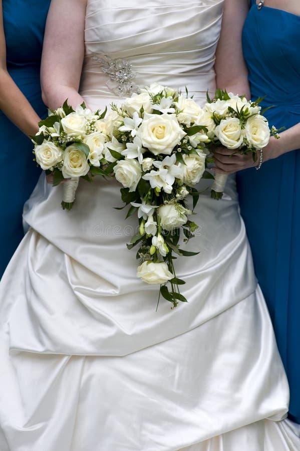 Novia y damas de honor que sostienen ramos de la boda imagenes de archivo