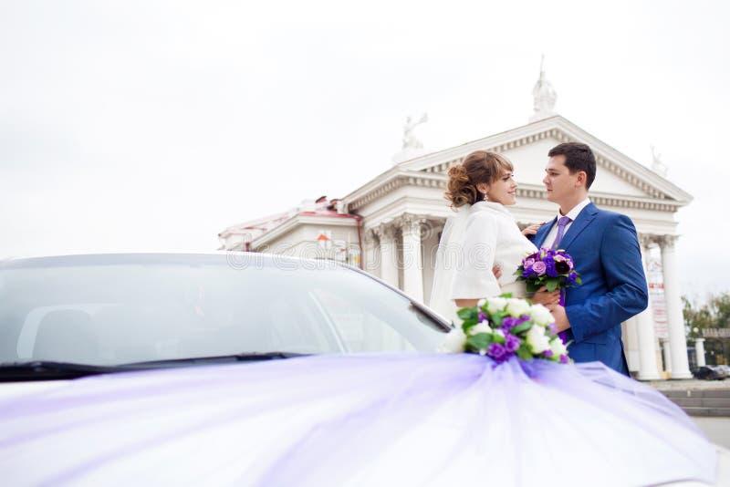 Novia y novio cerca del coche imagen de archivo libre de regalías