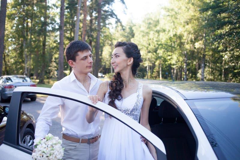 Novia y novio cerca del coche, par feliz joven fotos de archivo libres de regalías