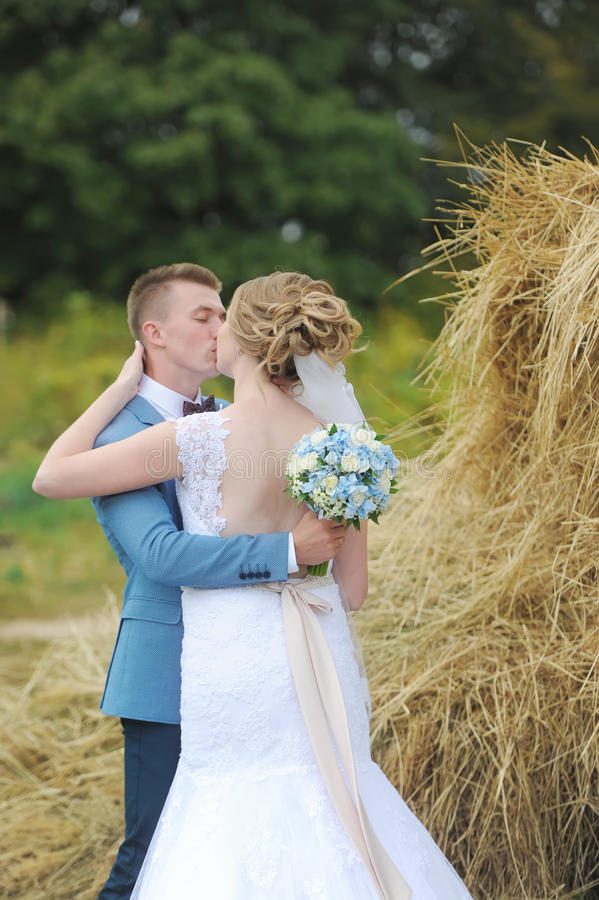 Novia y novio cerca del heno en un campo rural Beso de recienes casados fotografía de archivo