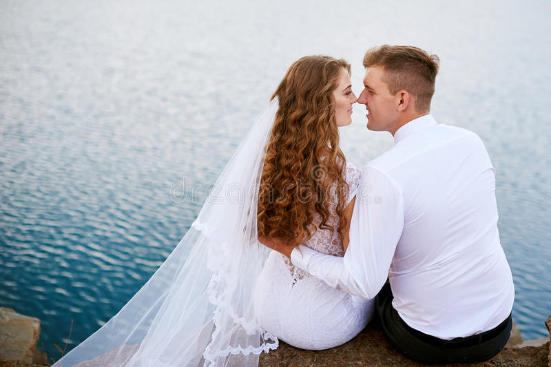 Novia y novio cerca del lago en día de boda fotografía de archivo