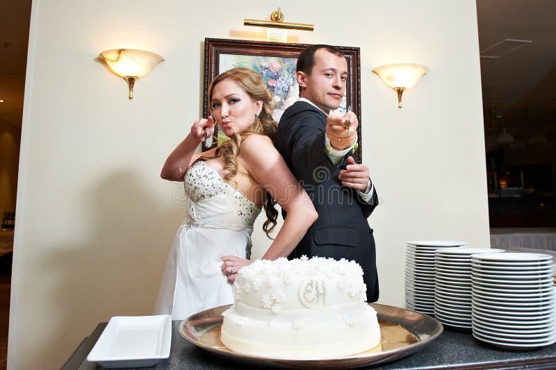Novia y novio cerca del pastel de bodas imágenes de archivo libres de regalías