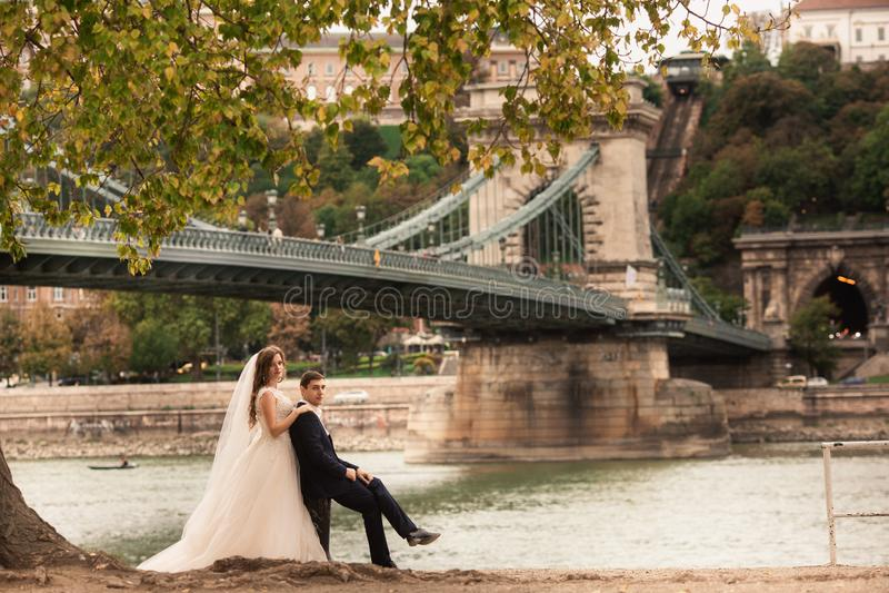 Novia y novio cerca del puente en Budapest Pares magn?ficos de la boda que caminan en la ciudad vieja de Budapest imagenes de archivo