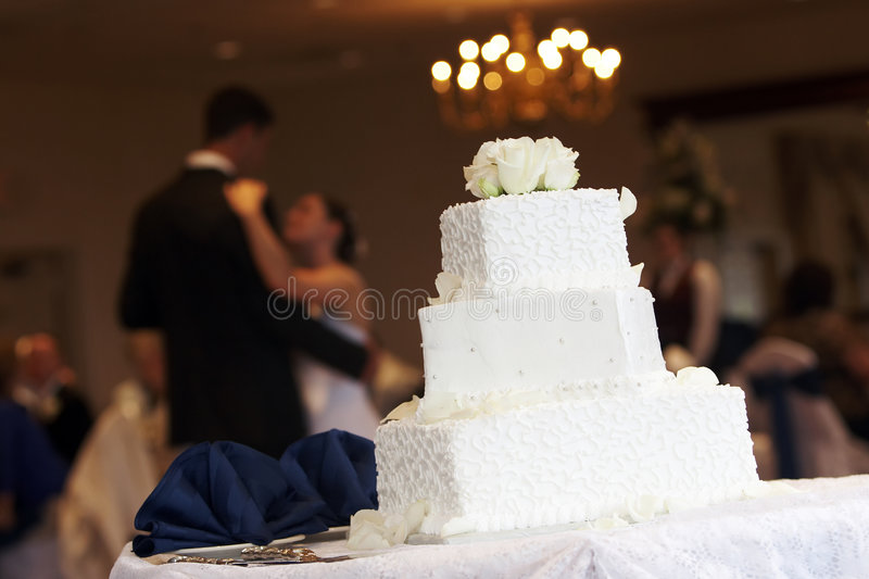 Novia y novio con la torta de boda foto de archivo