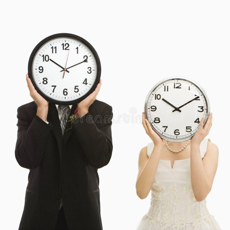 Novia y novio con los relojes. imagen de archivo