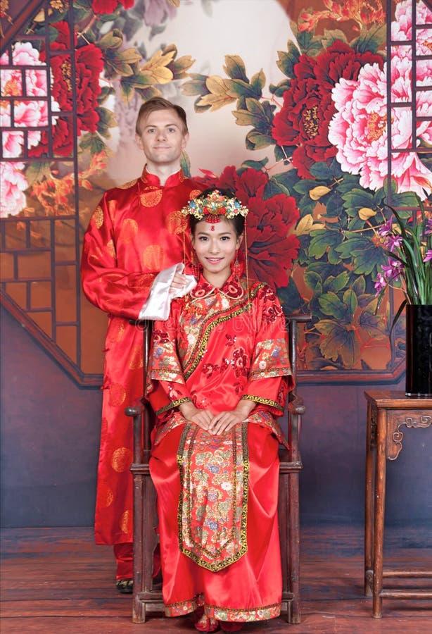 Novia y novio de la raza mixta en el estudio que lleva los equipos de la boda del chino tradicional imagenes de archivo