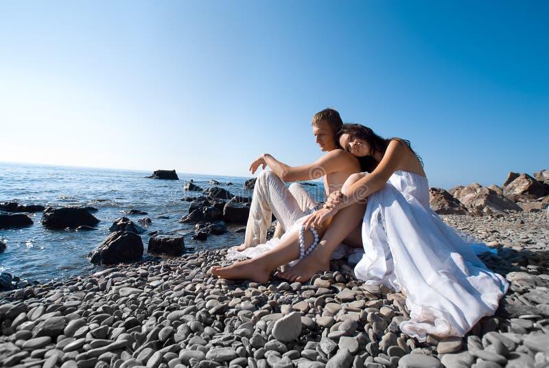 Novia y novio en costa de mar