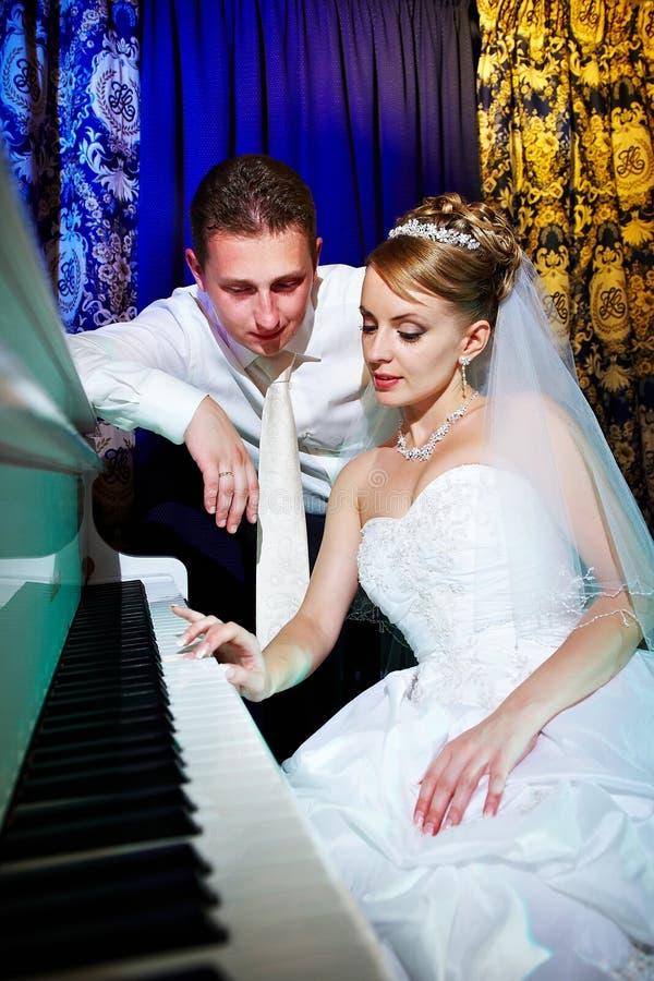 Novia y novio en el piano imagen de archivo libre de regalías