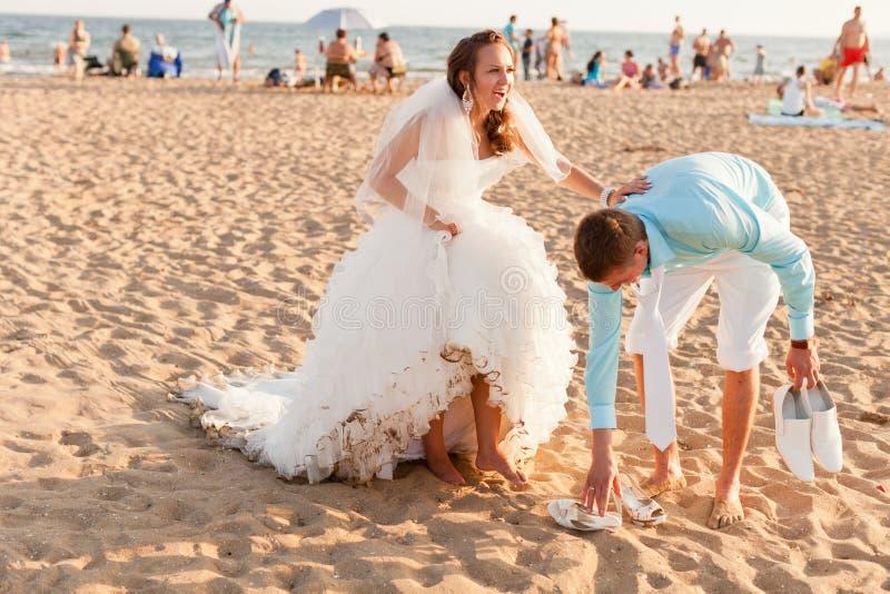 Novia y novio en la playa apretada imagen de archivo libre de regalías