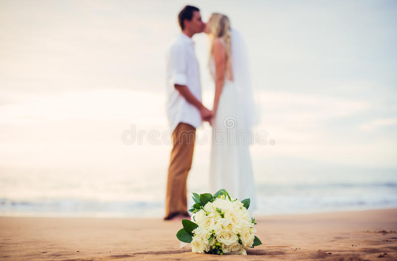 Novia y novio en la playa en la puesta del sol foto de archivo libre de regalías
