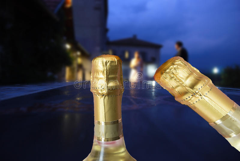 Novia y novio en la puesta del sol con las botellas del champán imágenes de archivo libres de regalías