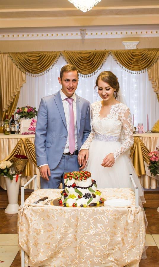 Novia y novio en la recepción nupcial que corta la torta imagenes de archivo