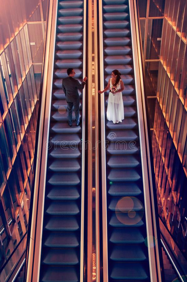 Novia y novio en las escaleras móviles fotografía de archivo