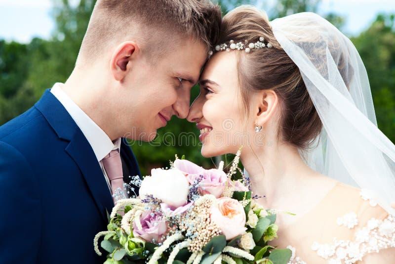 Novia y novio en un parque Besando a los recienes casados novia y novio de los pares en la boda en bosque del verde de la natural fotos de archivo libres de regalías