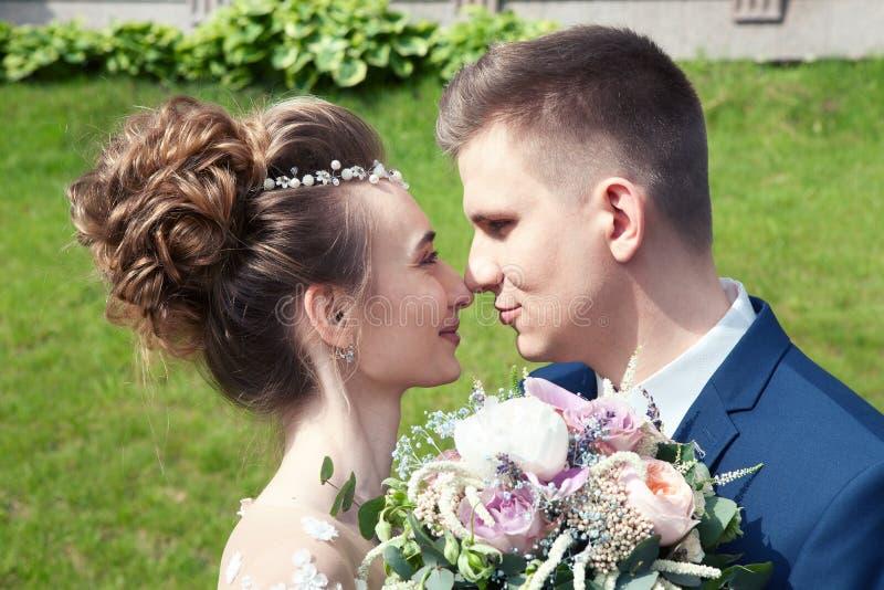 Novia y novio en un parque Besando a los recienes casados novia y novio de los pares en la boda en bosque del verde de la natural imagen de archivo libre de regalías