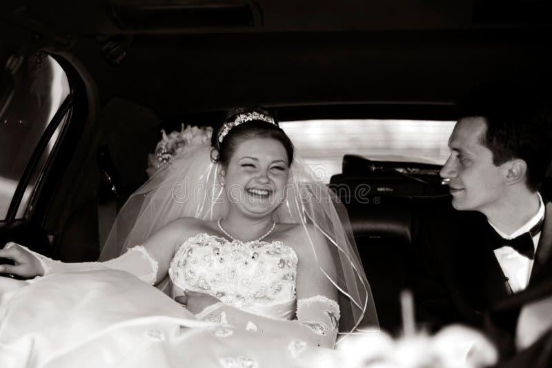 Novia y novio en una limusina imagenes de archivo