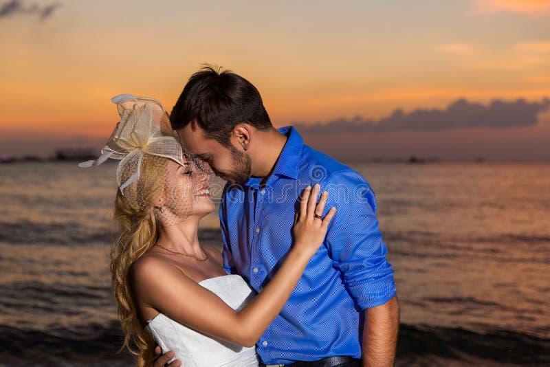 Novia y novio en una playa tropical con la puesta del sol en el backg imagen de archivo libre de regalías