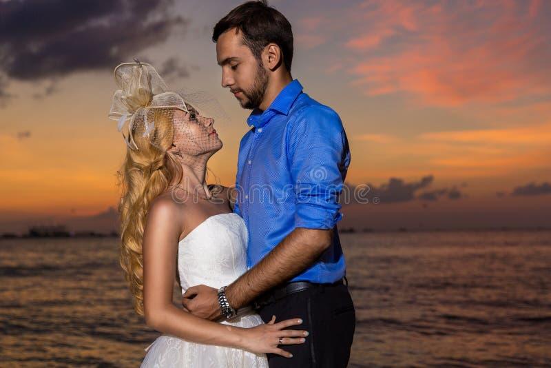 Novia y novio en una playa tropical con la puesta del sol en el backg imagen de archivo