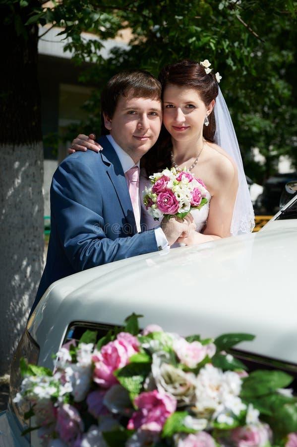 Novia y novio felices cerca del limo de la boda foto de archivo