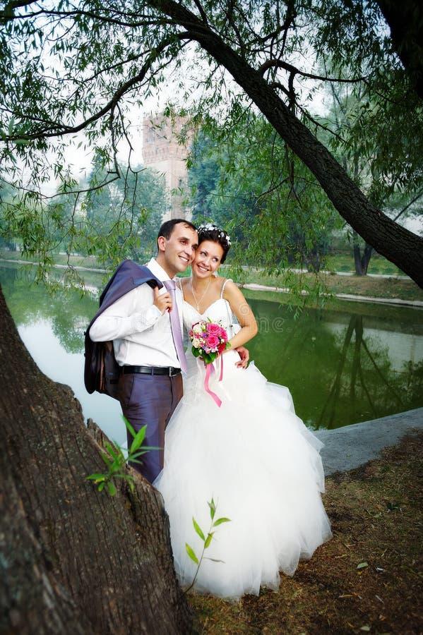 Novia y novio felices en la costa del lago imagen de archivo