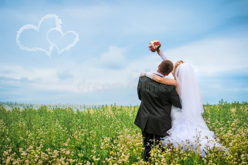 Novia y novio felices en un campo hermoso entre las flores foto de archivo