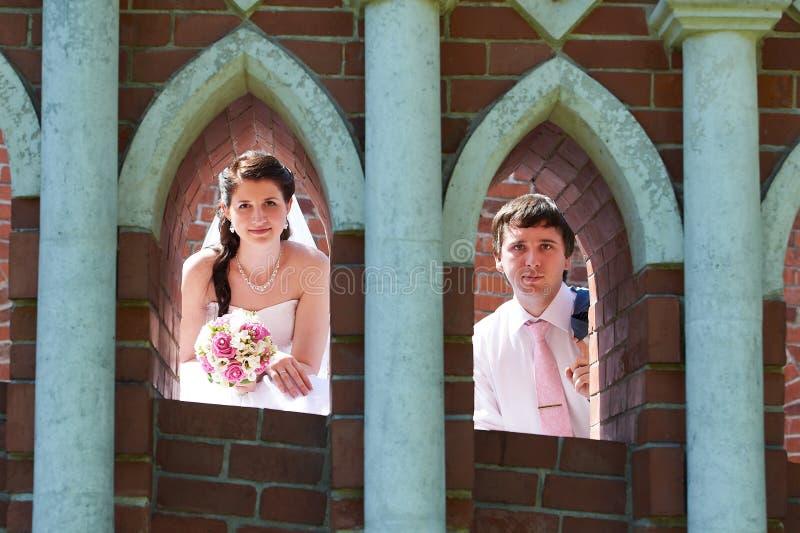 Novia y novio felices en ventanas de la pared de ladrillo fotografía de archivo libre de regalías