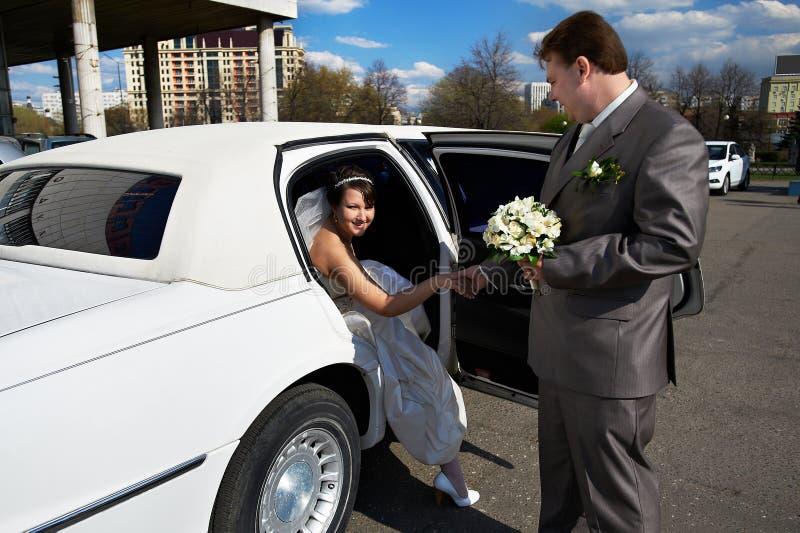 Novia y novio felices fuera de la limusina de la boda foto de archivo libre de regalías
