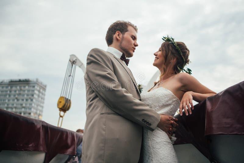 Novia y novio felices jovenes en un barco en el fondo de edificios fotografía de archivo libre de regalías