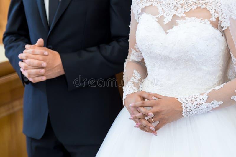 Novia y novio irreconocibles en la iglesia durante la ceremonia de boda cristiana Las manos de novias se cierran para arriba en fotografía de archivo libre de regalías