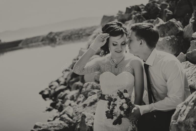 Novia y novio jovenes sonrientes felices, caminando en la playa, el besarse, abrazando ceremonia de boda cerca de rocas, océano fotos de archivo libres de regalías