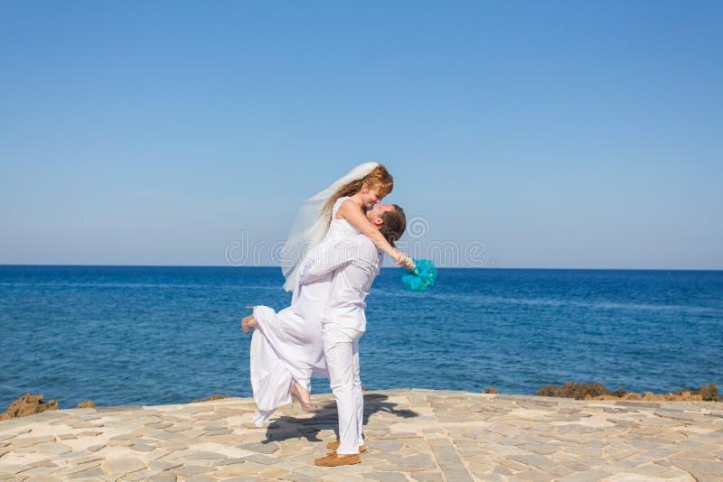 Novia y novio por el mar en su día de boda imagen de archivo libre de regalías