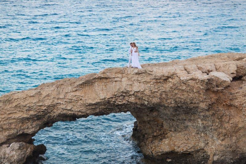 Novia y novio por el mar en su día de boda foto de archivo
