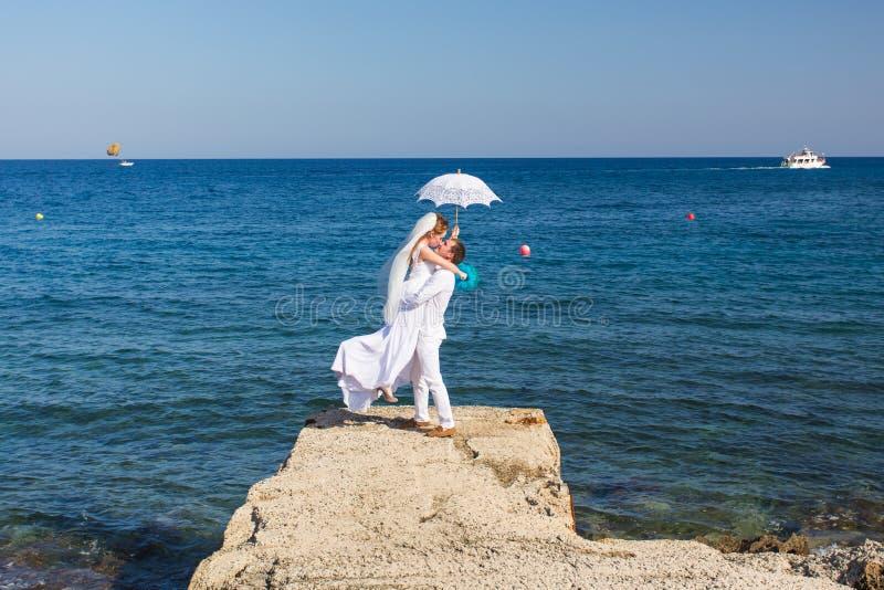 Novia y novio por el mar en su día de boda imagenes de archivo