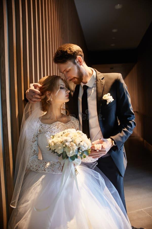 Novia y novio que abrazan y que se besan mientras que se coloca en las escaleras Casandose, trate el abrazo con suavidad del homb imágenes de archivo libres de regalías