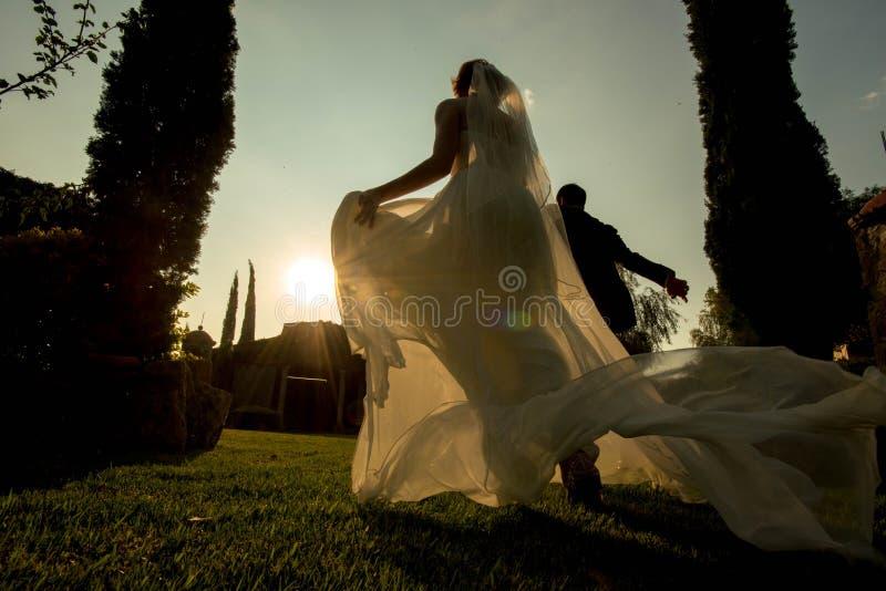 Novia y novio que corren lejos en la puesta del sol, boda en la puesta del sol, boda del jardín de la hacienda en México fotografía de archivo libre de regalías