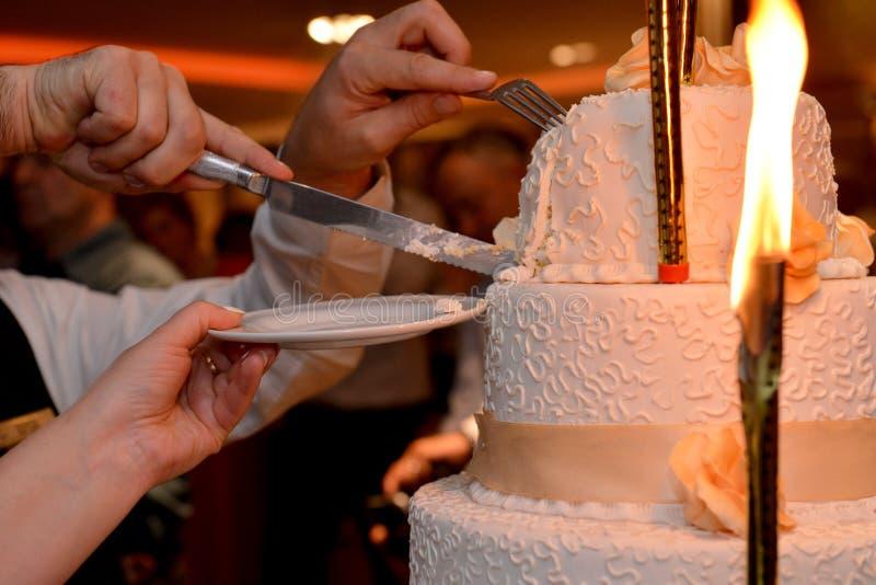 Novia y novio que cortan su pastel de bodas foto de archivo libre de regalías